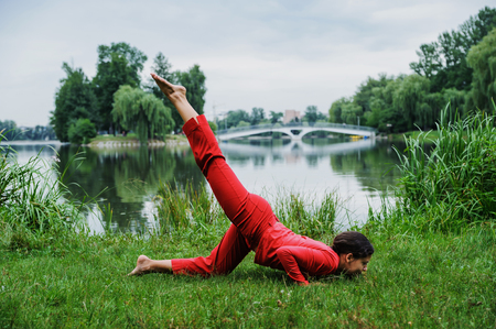 Beautiful young woman performing yoga exercises on the lake. Ashtanga namaskar Фото со стока