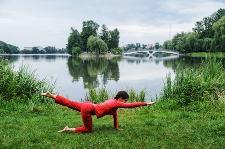Beautiful young woman performing yoga exercises on the lake. Marjariasana Фото со стока