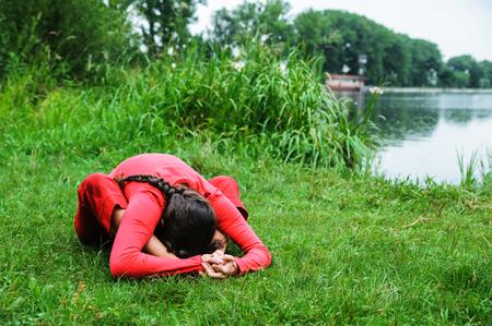 Beautiful young woman performing yoga exercises on the lake. Kurmasana Фото со стока