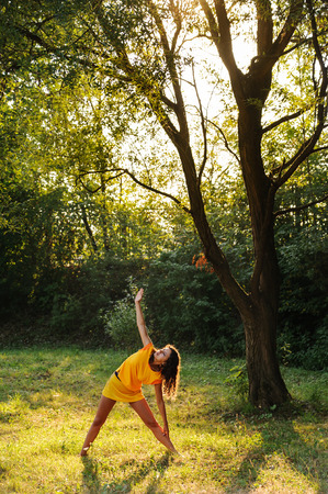 Young beautiful woman doing yoga exercise under the tree Фото со стока