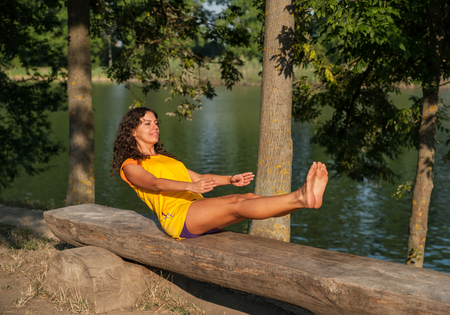 Beautiful young woman performing yoga exercises on the lake.