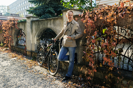 The man is standing by the fence with wild grapes. He is holding the bike.