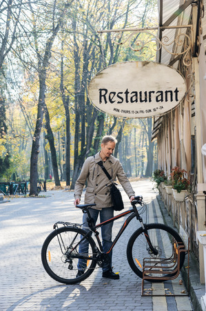 The man is parking his bike near the restaurant.