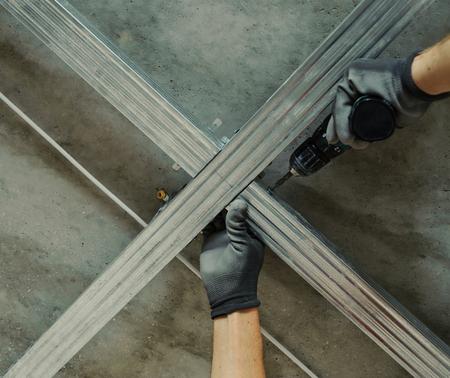 Man assembles profile metal frame for plasterboard ceilings