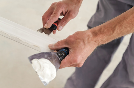 Installation of ceiling moldings. Worker puts glue on plastic molding for further fixing it to the ceiling Фото со стока