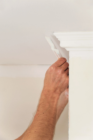 Installation of ceiling moldings. Worker fixes the plastic molding to the ceiling Фото со стока
