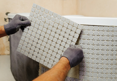 Installatie van mozaïektegels. De arbeider bevestigt de tegel aan de basis
