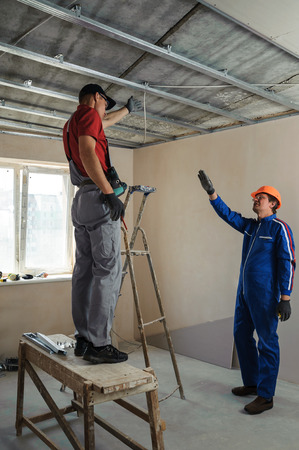 Foreman gives instructions to workers as a drywall ceiling mount
