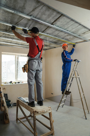 Workers measure metal frame for plasterboard ceilings