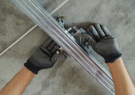 Worker assembles profile metal frame for plasterboard ceilings