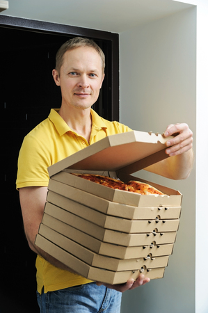 Food delivery home.  The man is holding boxes with pizzas in the doorway. The top box has been opened.