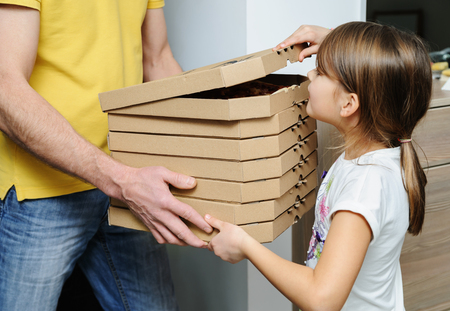 Food delivery home.  The man is holding boxes with pizzas. The girl is looking into the top box. Фото со стока
