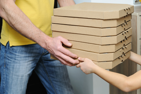 Food delivery home. Mans and childrens hands are holding boxes with pizzas. Фото со стока
