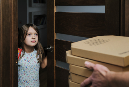 The girl opened the door to get her pizza. The pizza deliverer is holding the boxes in his hands. Фото со стока - 92700205