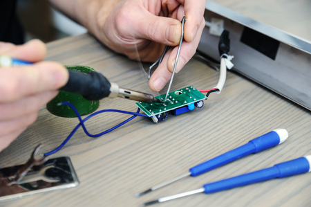 The man is repairing the power supply of the lamp. He is holding an electronic board and a soldering iron.