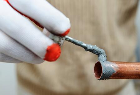 Un ouvrier applique du flux à l'extérieur du tube de cuivre.