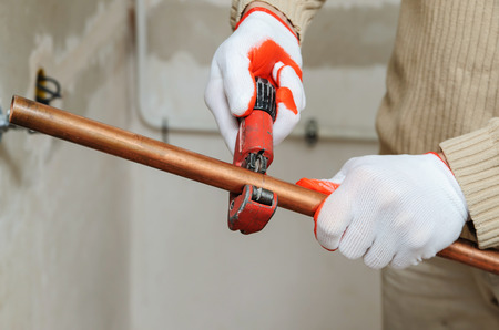 The worker is using a copper pipe cutter to cut the pipes of the desired size.