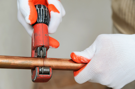 The worker is using a copper pipe cutter to cut the pipes of the desired size. Фото со стока - 92760812