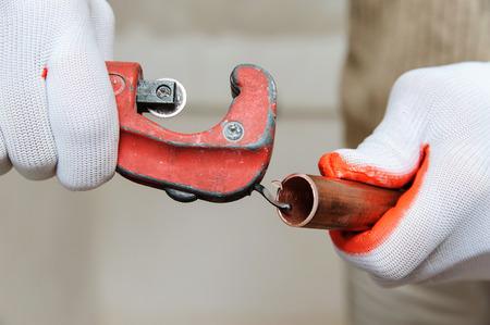 作業者は、銅管を切断した後、バリを除去しています。