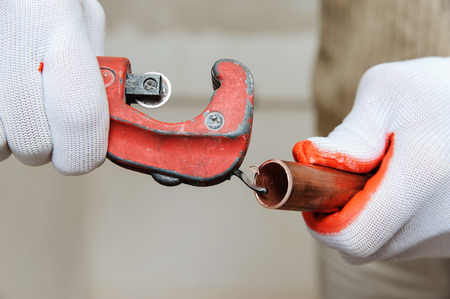 A worker is removing the burr after cutting the copper tube.