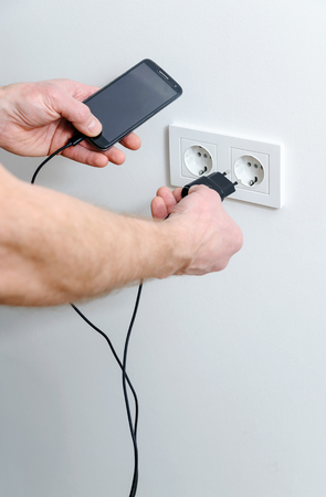 A man is inserting the plug into the wall socket to charge the smartphone. Stockfoto