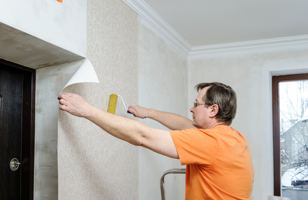 Glueing wallpapers at home. The man is using a roller for better adhesion of wallpaper.
