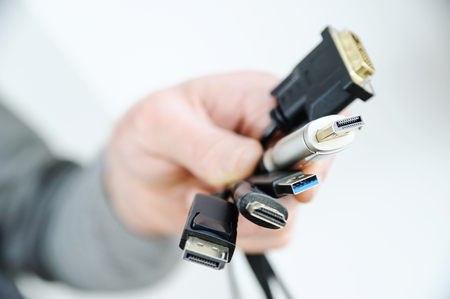 There are various cords and plugs in the hand of a man.