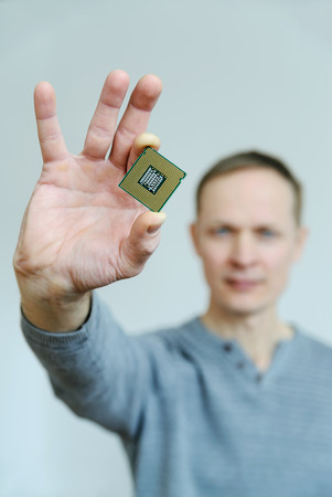 The processor is in the mans hand. A man is holding a processor between two fingers.