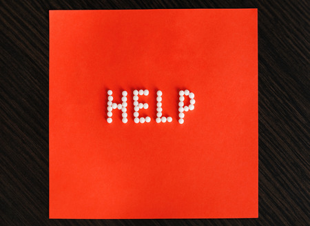 Help Homeopathy. The word help set out with homeopathic balls on a red background.