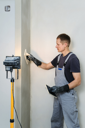 Worker makes final smoothing plaster on the wall using a plastic and Felt floats.
