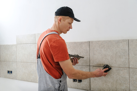 Worker holding a rubber float and filling joints with grout. Фото со стока