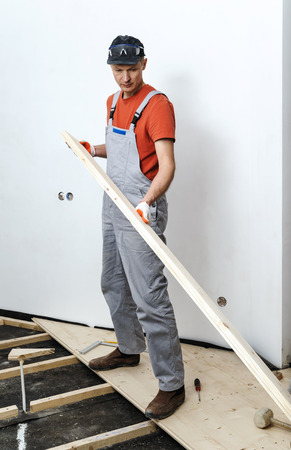 Installation of the wooden floor. Worker holds the wooden floorboards.