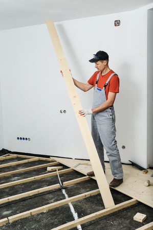 Installation of the wooden floor. A worker holds the wooden floorboards.