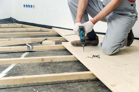 Installation of wooden floors. Worker twisting screw into the floor board. Фото со стока