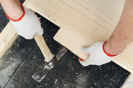 Installation of the wooden floor. A worker pushes the board to the board, knocking with a hammer.