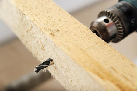 Drill passes through the wood bar creates a hole.