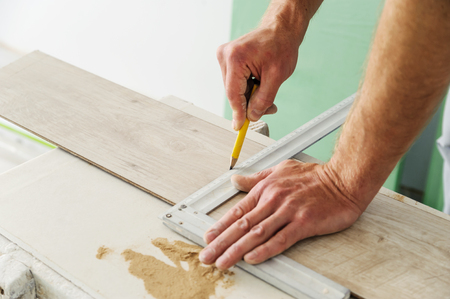 Installing laminate flooring. Worker measures off a piece of board to cut.