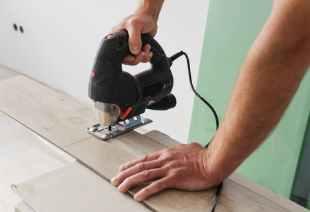 Installing laminate flooring. Worker cut part of the board with an electric jigsaw