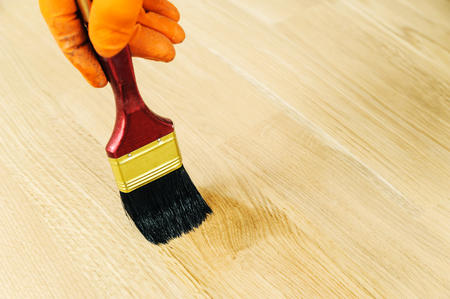 Lacquering wood floors. Use brush for coating floors.