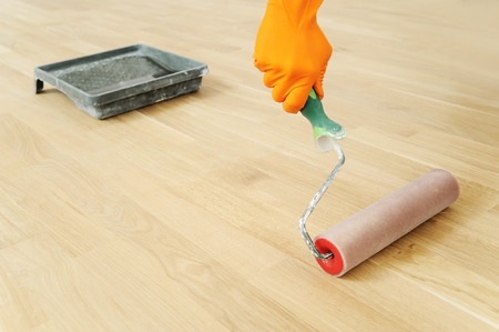 Lacquering wood floors. Use roller for coating floors. Stockfoto