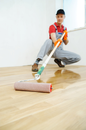 Lacquering wood floors. Use roller for coating floors. Stock fotó