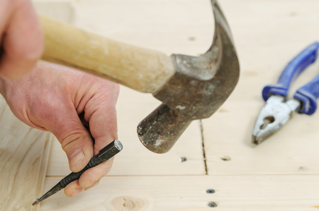 Laying hardwood parquet. Worker attaches the board to put a nail wooden base.