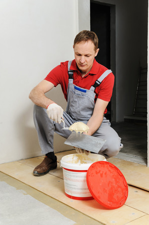 Laying plywood on the floor. A worker puts glue for gluing of the plywood Фото со стока