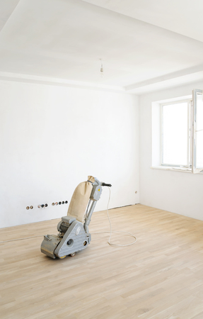The grinding machine for wooden parquet floors on a oak parquet. Фото со стока