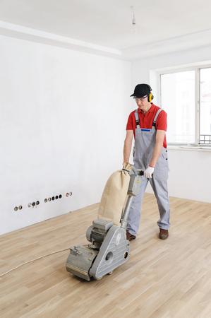 Worker polishing hardwood parquet floor with grinding machine.