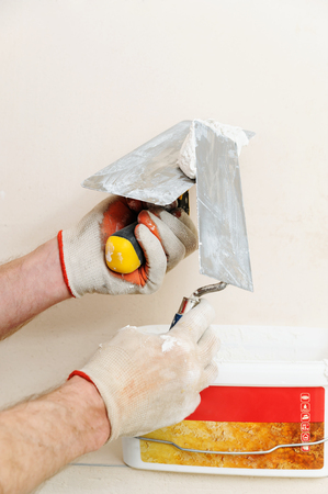 Decorative plaster coating. Man takes plaster from container. Фото со стока