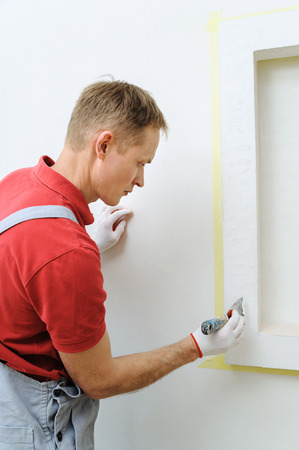 Decorative plaster coating. Man does ragged texture on the wall using a spatula. Фото со стока