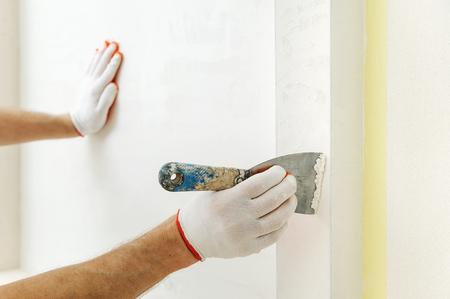Decorative plaster coating. Man does ragged texture on the wall using a spatula. Фото со стока