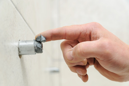 Plumber putting a paste sealant on the threads pipe.