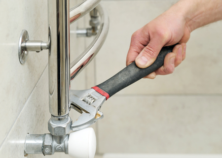 Plumber  sets  valve for towel warmer. It uses an adjustable wrench. Фото со стока